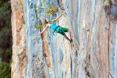 垂悬在垂直的自然墙壁上的极端体育运动员 免版税库存图片
