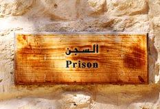 垂悬在墙壁上的一个古板的木监狱标志。 免版税库存图片