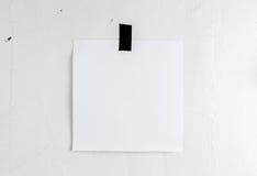 垂悬在墙壁上的一卷磁带上的空白的白色海报 模板backg 库存图片