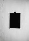 垂悬在墙壁上的一卷磁带上的空白的黑海报 模板backg 免版税图库摄影