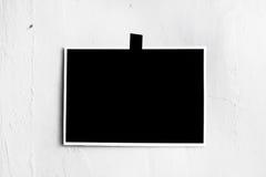 垂悬在墙壁上的一卷磁带上的空白的黑海报 模板backg 免版税库存照片