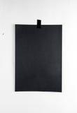 垂悬在墙壁上的一卷磁带上的空白的黑海报 模板backg 免版税库存图片