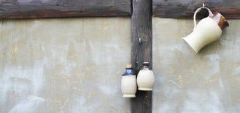 垂悬在墙壁上的三个水罐 免版税图库摄影