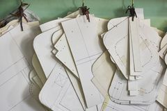 垂悬在墙壁上的专业裁缝纸模板集合在车间 制造的皮革物品,工艺产品 库存图片