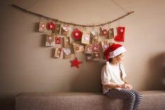 垂悬在墙壁上的出现日历 孩子的小礼物惊奇 作为矮人打扮的女孩 免版税库存图片