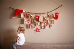 垂悬在墙壁上的出现日历 孩子的小礼物惊奇 免版税库存照片