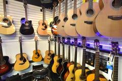 垂悬在墙壁上的吉他在商店 免版税图库摄影