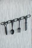 垂悬在墙壁上的塑料厨房工具 免版税库存照片