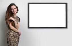 垂悬在墙壁上的妇女和电视 免版税图库摄影