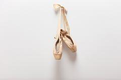 垂悬在墙壁上的对老芭蕾舞鞋 免版税库存照片