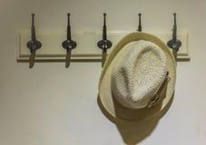垂悬在墙壁上的帽子 免版税库存照片
