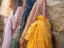 垂悬在墙壁上的老和使用的渔夫网的图象 库存照片