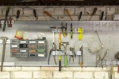 垂悬在墙壁上的老工具在金属制品车间,工具架子aga 库存图片