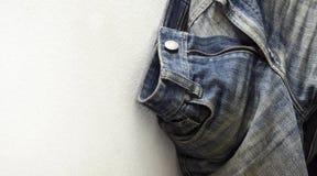 垂悬在墙壁上的蓝色老牛仔裤 免版税库存图片