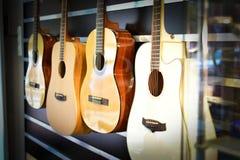 垂悬在墙壁上的西班牙声学吉他在音乐商店 库存图片