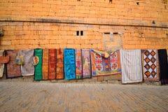 垂悬在墙壁的五颜六色的纺织品席子 免版税库存照片