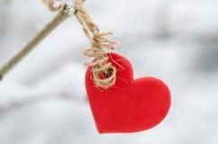 垂悬在多雪的树早午餐的红色心脏 免版税库存照片