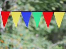垂悬在天空的多色的三角旗子在室外反对绿草的背景 免版税库存照片