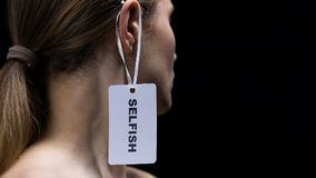 垂悬在女性耳朵的人手自私标签,显示不恭和感到羞耻 影视素材