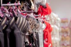 垂悬在女用贴身内衣裤内衣商店的胸罩行  做广告,销售,时尚概念 库存照片