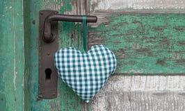 垂悬在婚姻的门把手的方格的绿色心脏形状, 图库摄影