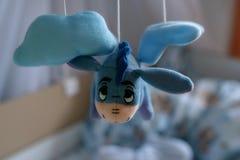 垂悬在婴孩` s小儿床上的可爱的蓝色长毛绒玩具 库存照片