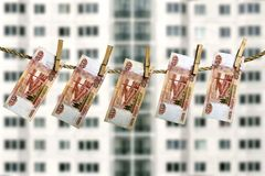垂悬在寓所背景的被弄脏的门面的晒衣绳的俄罗斯卢布钞票 图库摄影