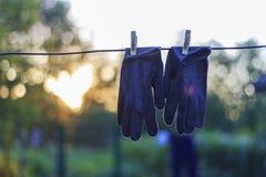垂悬在导线的Orking手套 库存照片