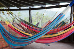 垂悬在屋顶下的五颜六色的吊床在热带天堂 免版税库存照片