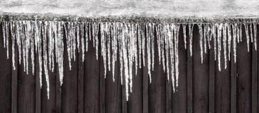 垂悬在屋顶的冰柱行  农村场面冬天 库存照片