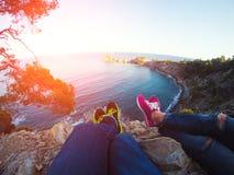 垂悬在岩石的夫妇腿 免版税库存图片