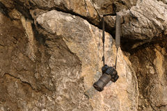 垂悬在岩石的老照相机 免版税库存照片