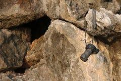 垂悬在岩石的老照相机 库存图片
