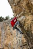 垂悬在峭壁的年轻男性登山人 免版税库存照片