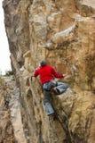垂悬在峭壁的年轻男性登山人 库存照片