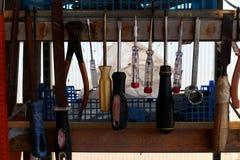 垂悬在工作者` s架子的老工具 螺丝刀、锤子和钳子 免版税库存图片