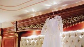 垂悬在床的美丽的白色婚纱 美好的酒店房间 好的光 股票视频