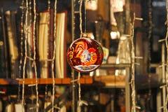 垂悬在店面窗口里的红色圣诞节球公鸡装饰新年和圣诞节在书店 免版税库存图片