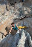 垂悬在异常的形状的岩石的微笑的男性极端登山人 免版税图库摄影