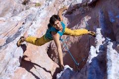 垂悬在异常的形状的岩石的微笑的男性极端登山人 库存照片