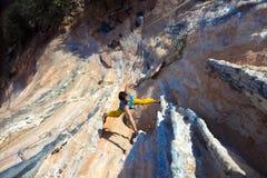 垂悬在异常的形状的岩石的成熟男性极端登山人 图库摄影
