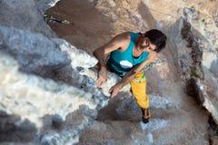 垂悬在异常的形状的岩石的成熟男性极端登山人 库存图片