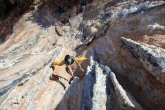 垂悬在异常的形状的岩石的成熟男性极端登山人 免版税库存图片