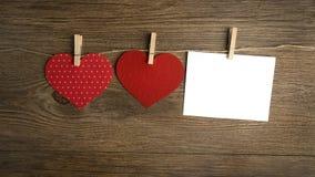垂悬在情人节卡片的晒衣绳的红色心脏 库存图片
