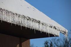 垂悬在房子屋顶的冰柱 库存图片