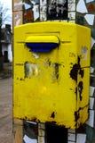 垂悬在房子的砖墙上的老黄色邮箱 免版税库存图片