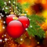垂悬在抽象杉树前面的三个红色圣诞节球 免版税库存照片