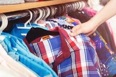 垂悬在挂衣架和一只女性手的五颜六色的衣裳举行a 库存照片