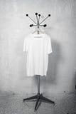 垂悬在挂衣架的白色T恤杉照片 垂直 库存照片