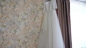 垂悬在挂衣架的美丽的白色婚礼礼服在窗口 股票录像